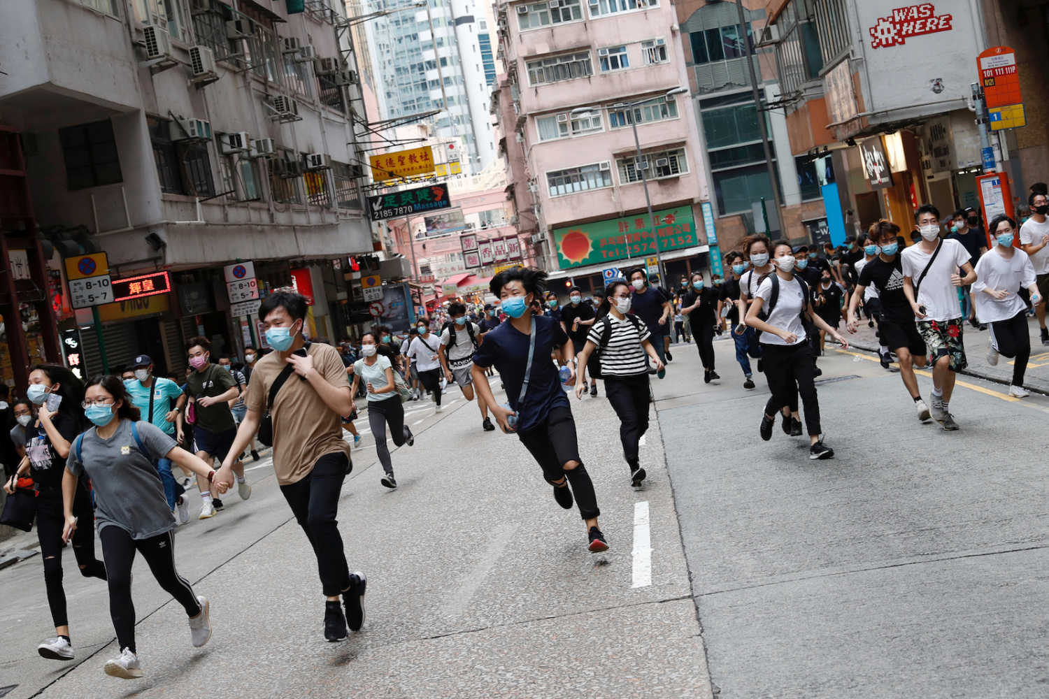 Anti-government protesters run after riot police disperse them in Hong Kong